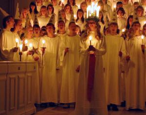 Joves cantant en el dia de Santa Llúcia i aquesta al capdavant amb la corona d'espelmes. Font: wikipedia